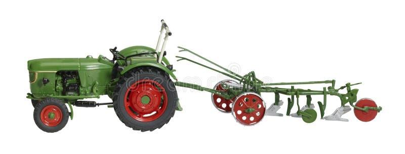 Tractor nostálgico del juguete con la reja de arado imagenes de archivo