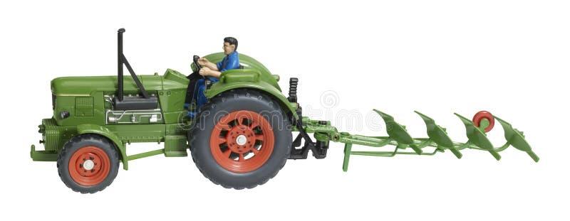 Tractor nostálgico del juguete con la reja de arado fotos de archivo