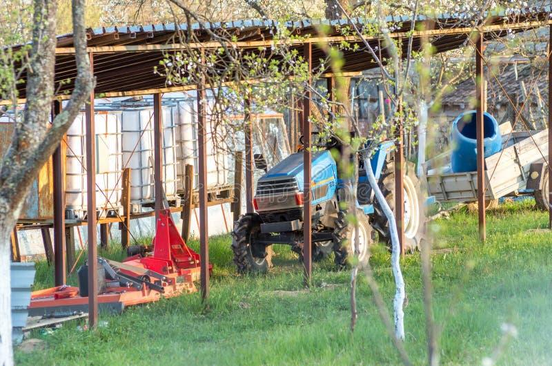 Tractor op een klein huislandbouwbedrijf voor groenten en vruchten Groen gras, bloeiende pruimbomen Blauwe tractor met stampers e stock afbeelding
