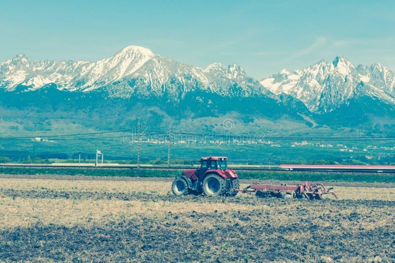 Download Tractor op gebied stock afbeelding. Afbeelding bestaande uit bergen - 54084075