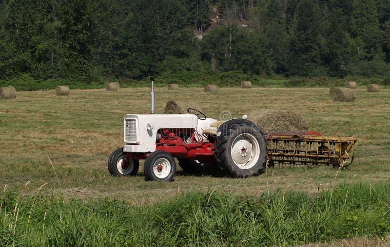 Tractor op hooigebied royalty-vrije stock afbeelding