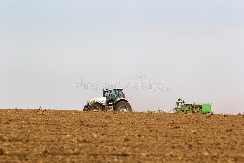Tractor operates on horizon line ploughed field on foreground. Distant tractor seeder on big wheels operates on horizon line against blue sky with ploughed field stock image