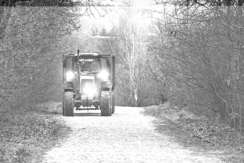Tractor on paved road rides with the lights around the woods, doing field work after twilight. Monohrom stock photo