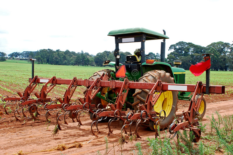 Tractor and plough. Image of farm workers ploughing and preparing a field for planting royalty free stock images