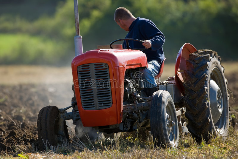 Tractor ploughing field. Farmer using an old tractor ploughing field royalty free stock image