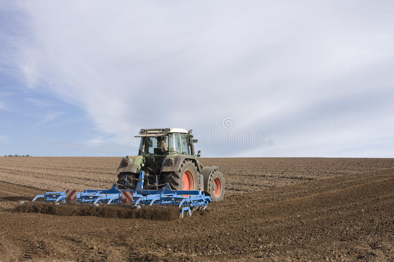 Tractor ploughing field. Rear view of tractor ploughing field in countryside with cloudscape background stock image