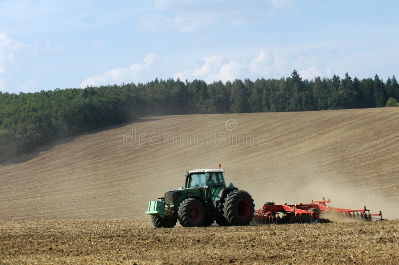 Tractor ploughing in field. Scenic view of tractor ploughing field in countryside with wood or forest in background stock photo