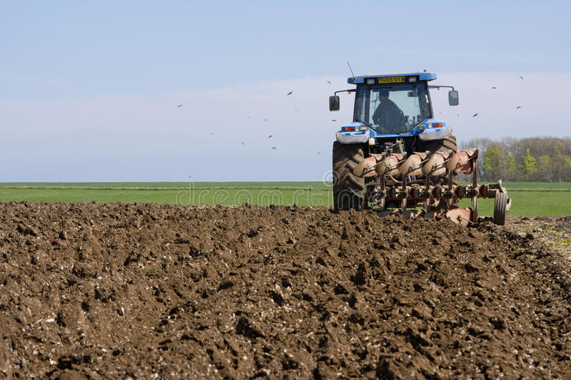 Tractor ploughing field royalty free stock photo