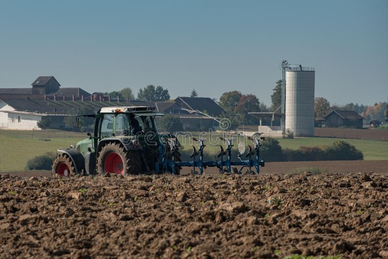 Tractor ploughing field with blurry farm in the background royalty free stock photos
