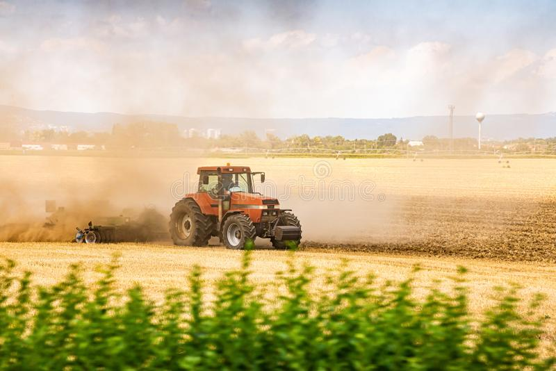 Tractor ploughing the field in sunset with dust in the air.  royalty free stock photography