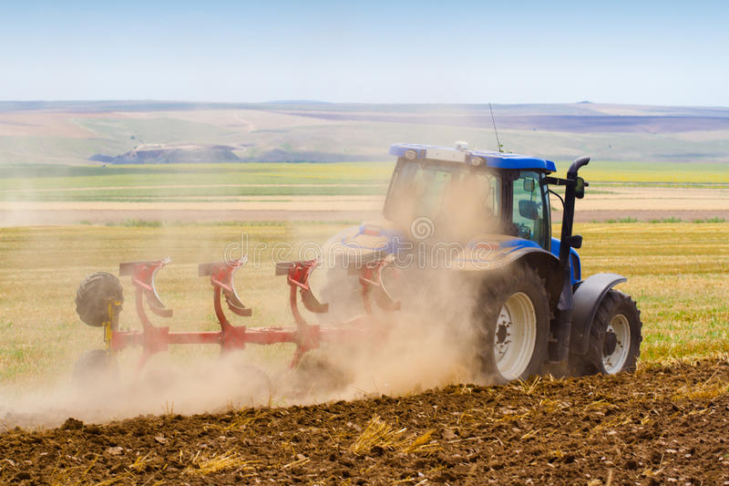 Tractor ploughing a field with trail of dust stock photos