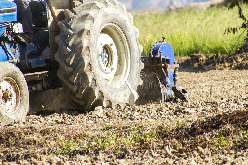 Tractor plowing field to prepare the cultivation stock photo