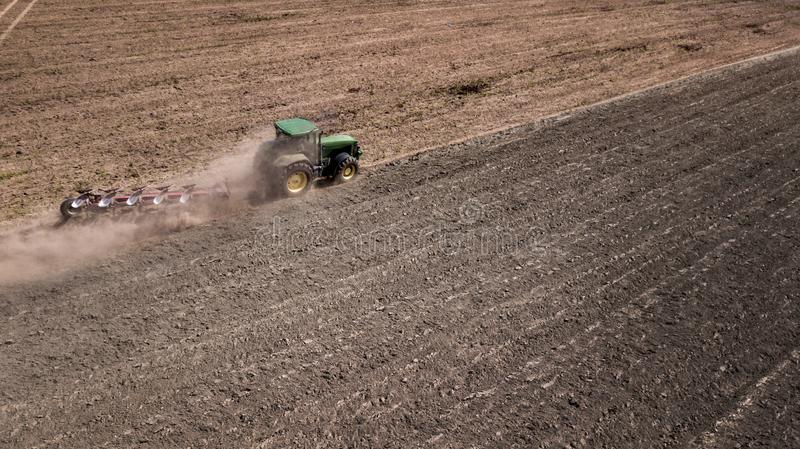 tractor plowing field top view, aerial photography with drone. royalty free stock photos