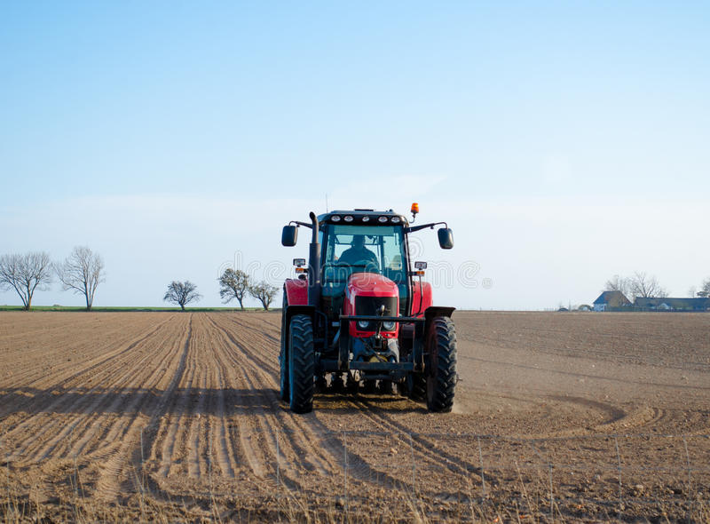 Tractor plowing fields stock photos