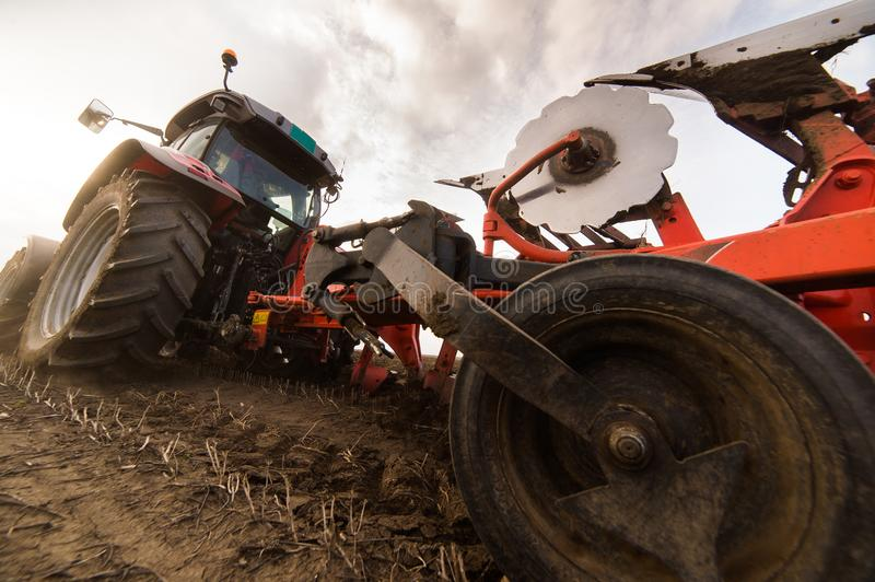 Tractor plowing fields -preparing land for sowing in autumn stock image