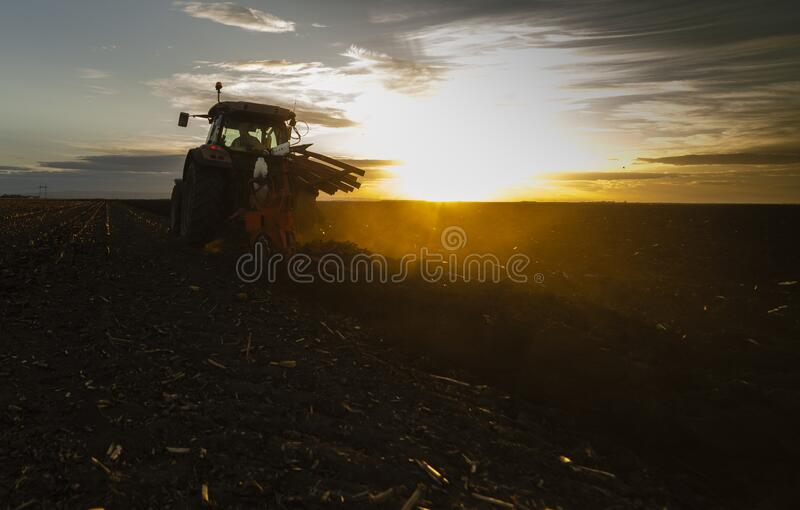 Tractor plowing fields in sunset royalty free stock photography