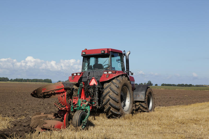 Tractor plowing at harvest time royalty free stock photo