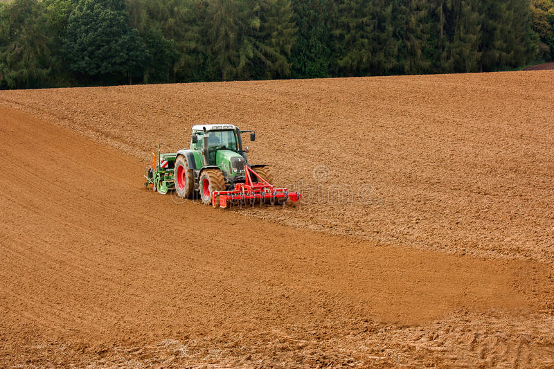 A tractor plowing soil. stock photo