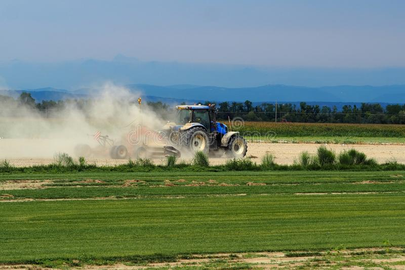 Tractor plows the field raising a large cloud of dust stock image