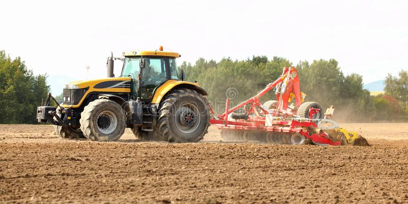 Tractor pulling ploughing / sowing trailer over dry field royalty free stock photography