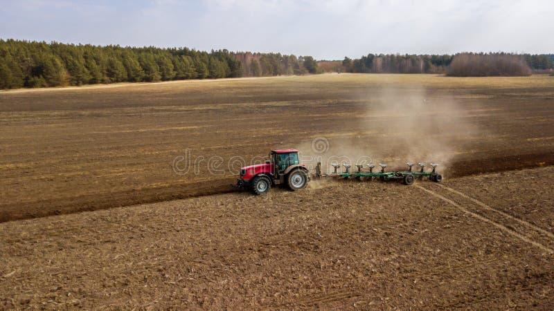 Tractor que ara vista lateral del campo fotos de archivo