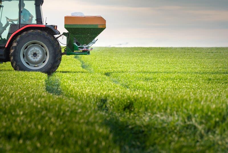 Tractor que fertiliza en campo foto de archivo