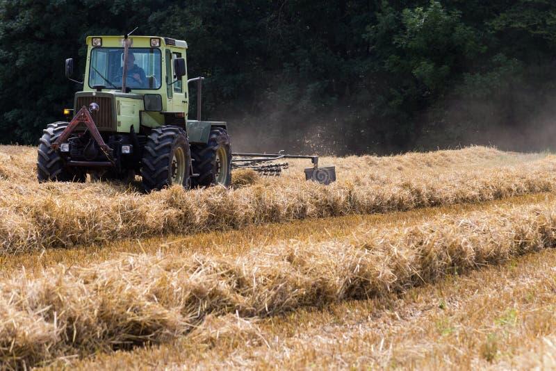 tractor que hace heno la paja en campo de maíz del verano foto de archivo