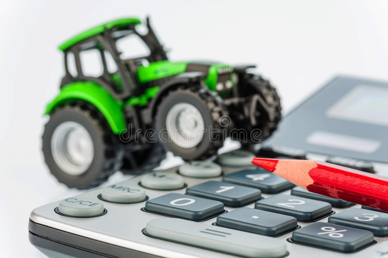 Tractor, red pen and calculator royalty free stock photo