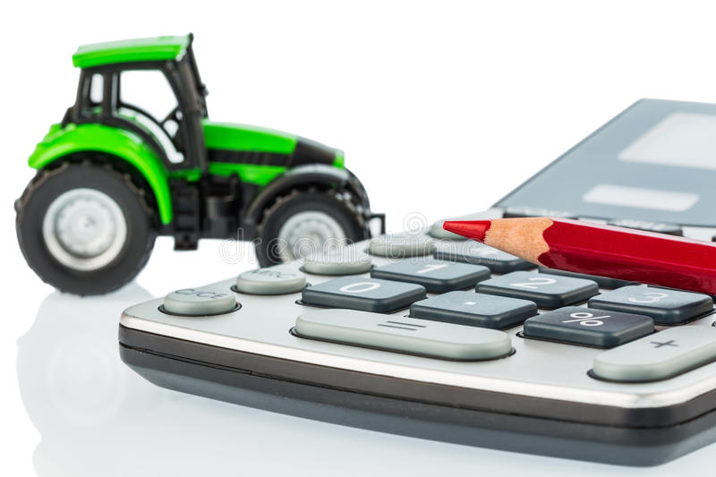 Tractor, red pen and calculator stock images