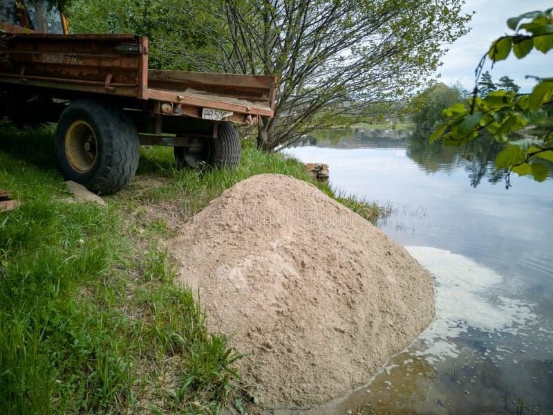 Tractor remolque que inclina una carga de la arena para crear la playa imagen de archivo libre de regalías
