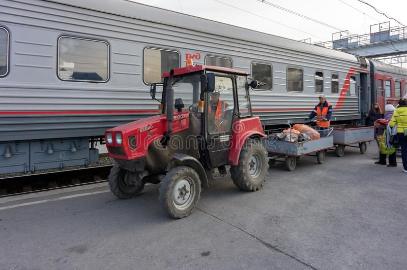 Tractor removes garbage from a train standing on the platform of the Siberian city Barabinsk railway station. BARABINSK/ NOVOSIBIRSK REGION/ RF- April 21, 2015 royalty free stock photo
