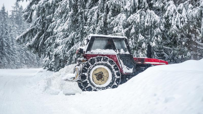 Tractor removing snow from large snowbanks next to forest road, after blizzard in winter royalty free stock photography