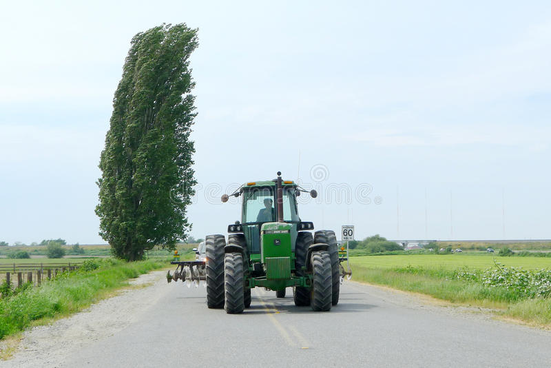 Tractor on the Road. This is taken in Canada.nnJohn Deere tractor royalty free stock photos