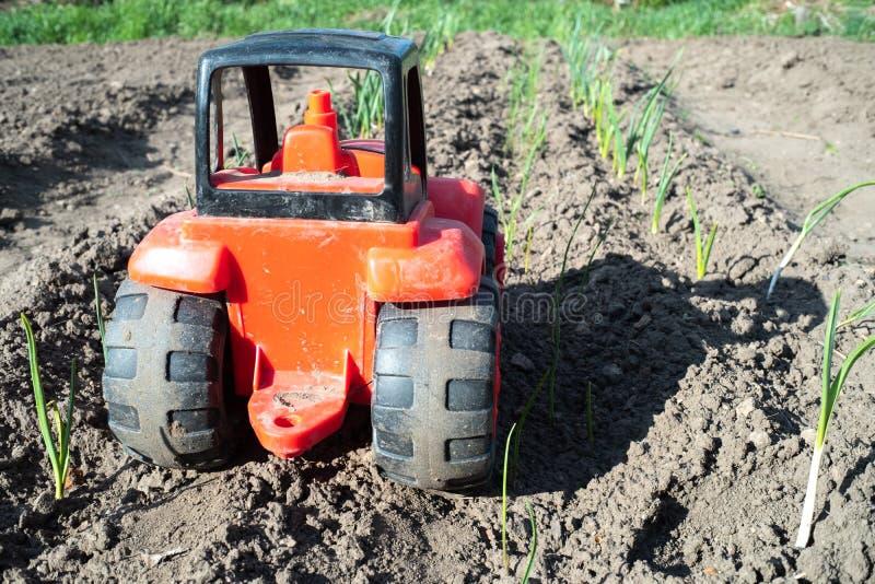 Tractor rojo con las ruedas negras, coche del juguete en el campo fotos de archivo libres de regalías