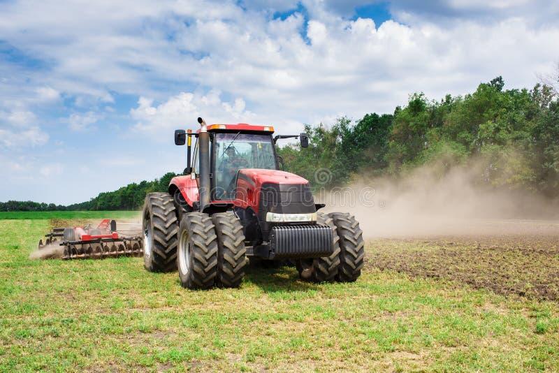 Tractor rojo de la tecnología moderna que ara un campo agrícola verde en primavera en la granja Trigo de la siembra de la máquina imagenes de archivo