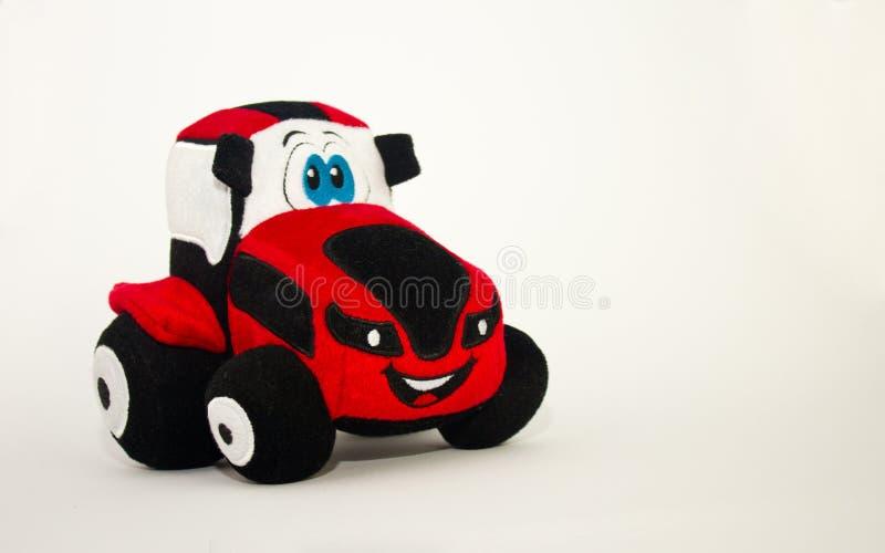 Tractor rojo del juguete lindo suave de los niños en un fondo blanco imagen de archivo
