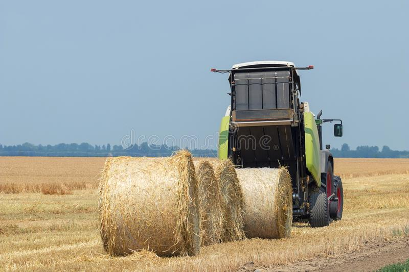 Tractor and round baler discharges. Straw Bales. royalty free stock images