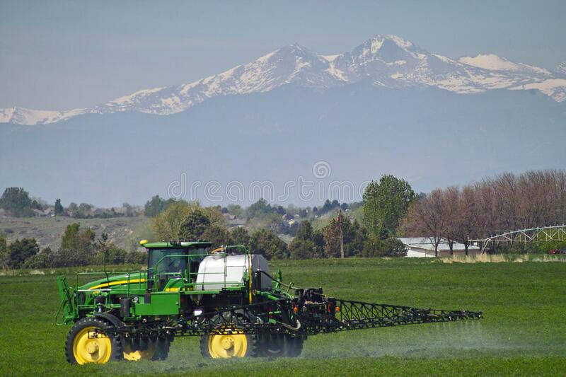 Tractor spraying chemicals on an alfalfa field stock photos
