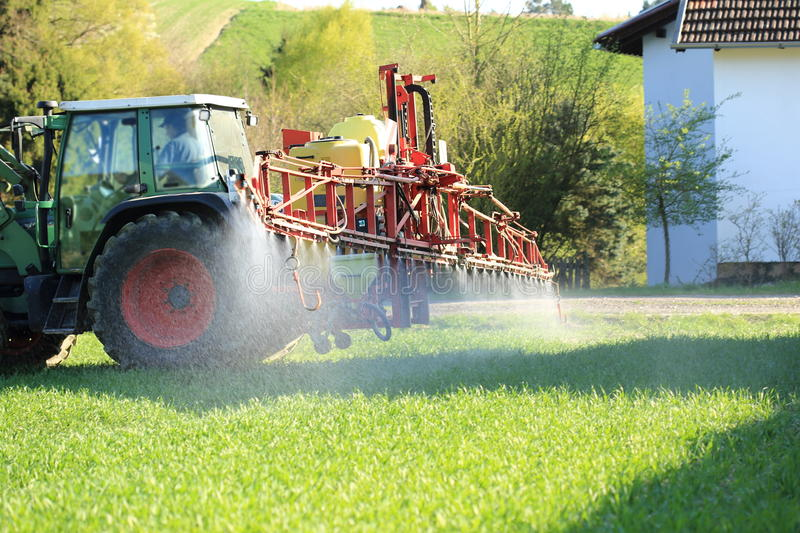 Tractor spraying pesticide near houses stock images