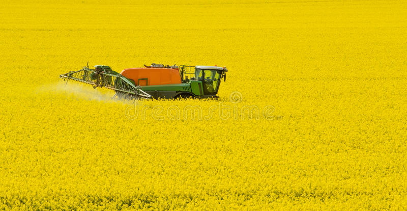 Tractor spraying field. By herbicides, pesticides or insecticides. Modern agriculture. is used to fuel like ingredient stock photography