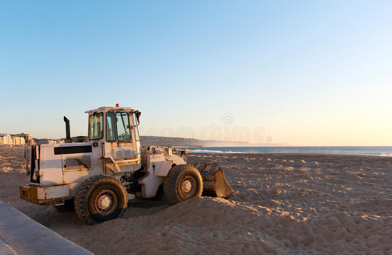 The tractor standing on the beach at sunset time. The tractor standing on the beach near ocean at sunset time stock photo
