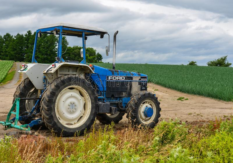 A tractor standing on the field. Furano, Japan - Jul 1, 2019. A tractor standing on the field in Furano, Japan. Furano located in the geographical center of royalty free stock image