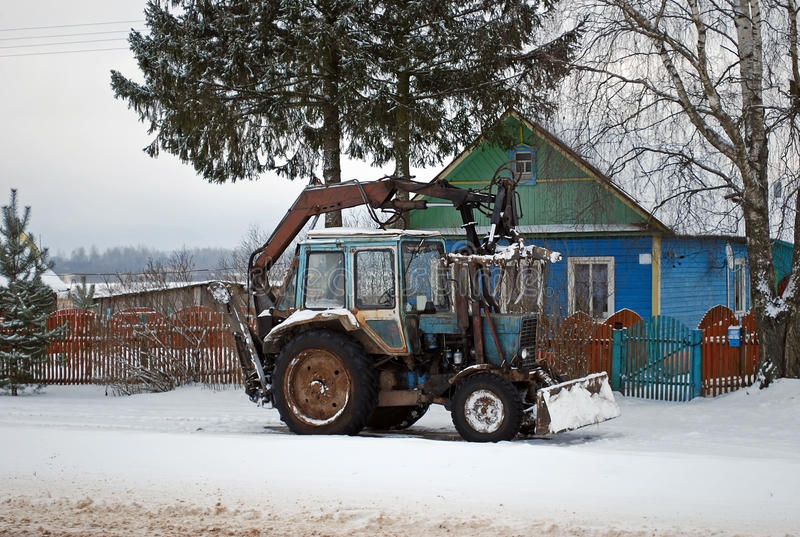 The tractor standing near a lodge in the village. Rural life. In the winter stock photo