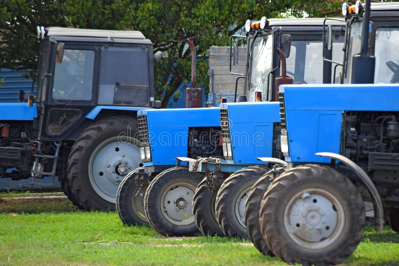 Tractor, standing in a row. Agricultural machinery. Parking of agricultural machinery royalty free stock image