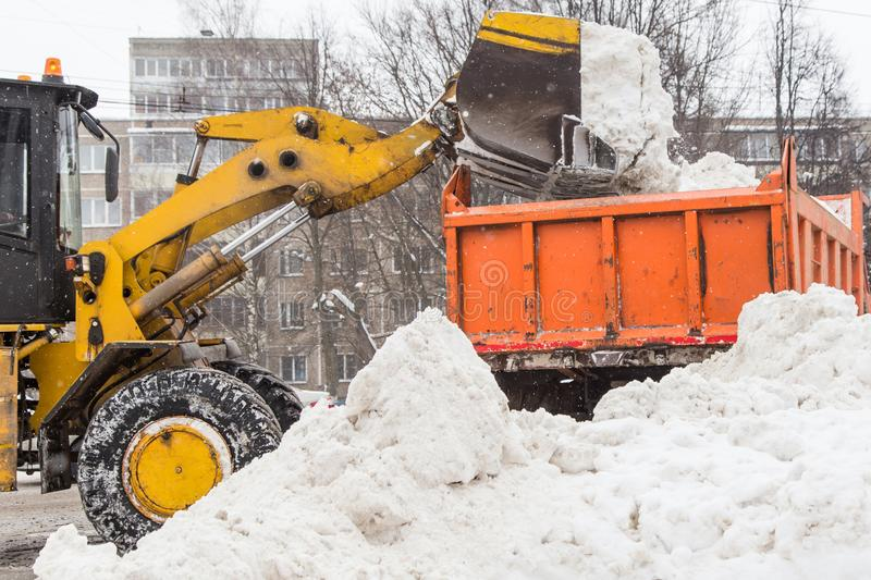 Tractor sweeper plowing the snow stock images