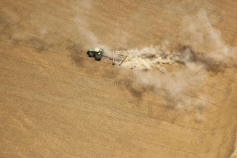 Tractor tilling soil. Aerial view of a tractor tilling the soil stock images