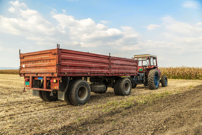 Tractor with trailer standing. In a field waiting for harvest stock images