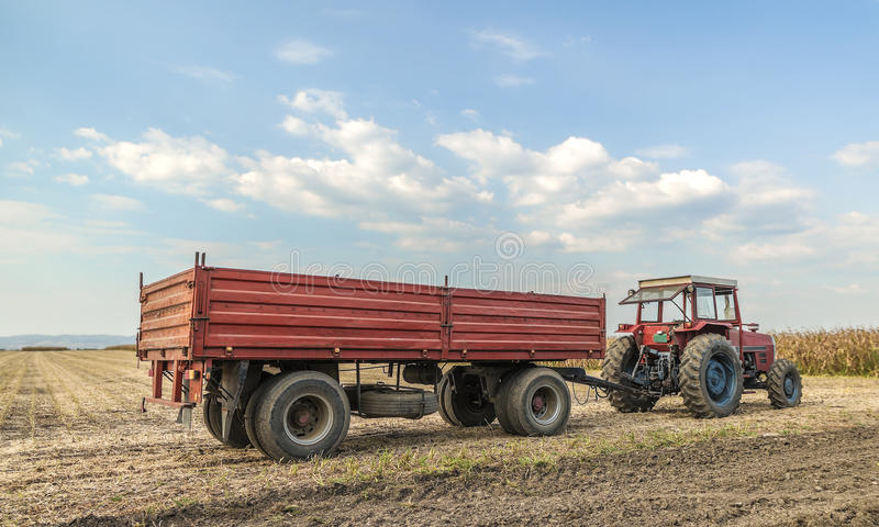 Tractor with trailer standing. In a field waiting for harvest royalty free stock photo