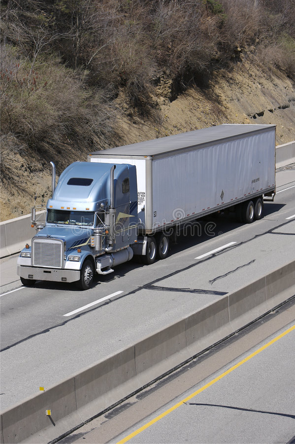 Tractor Trailer Truck. Light Blue Tractor Trailer Truck with White Trailer on the Freeway royalty free stock photos