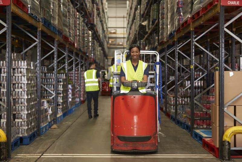 Tractor van het vrouwen de werkende slepen in een bezig distributiepakhuis royalty-vrije stock fotografie